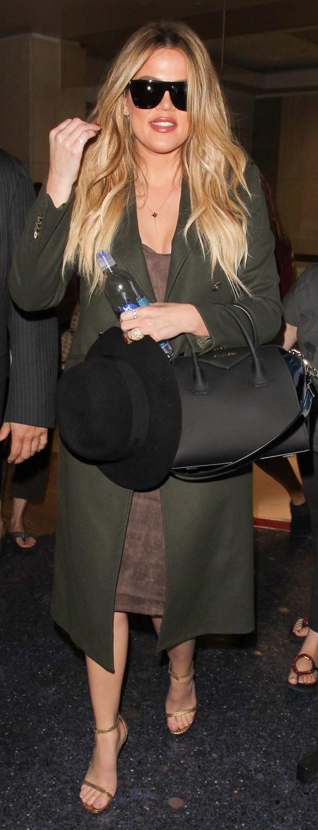 Khloe Kardashian in green trenchcoat at LAX airport 28 april