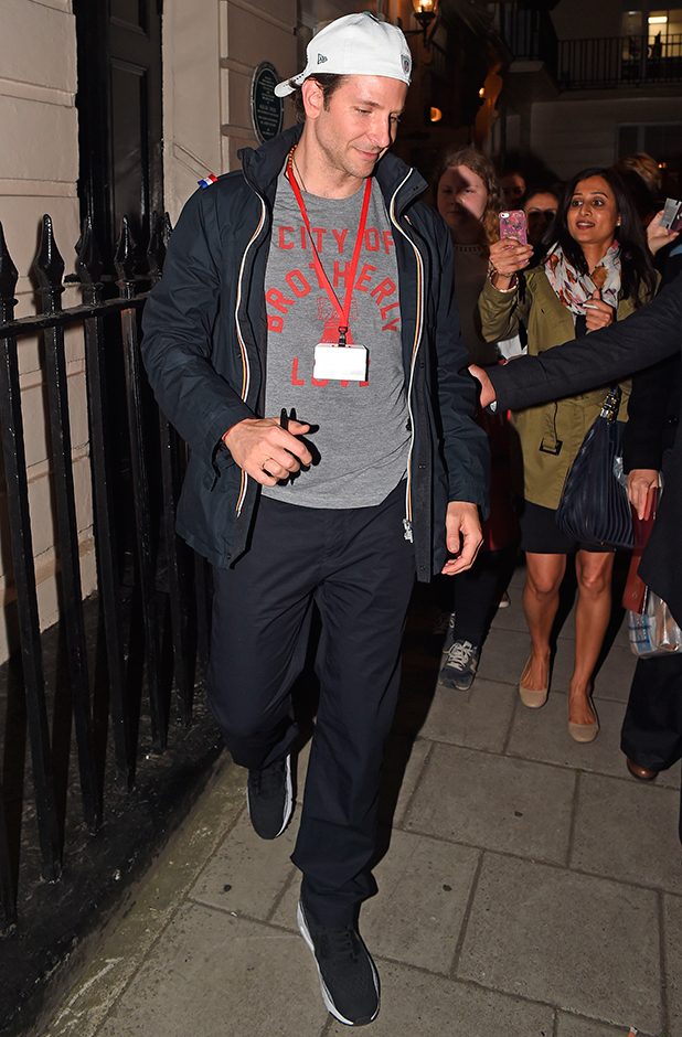 Bradley Cooper takes photos with fans, as he leaves the Theatre Royal Haymarket, having performed in a production of 'The Elephant Man'