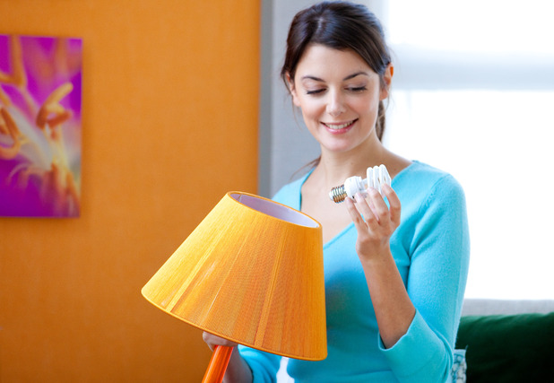 Woman changing a lightbulb. New survey says we feel like an adult at 27