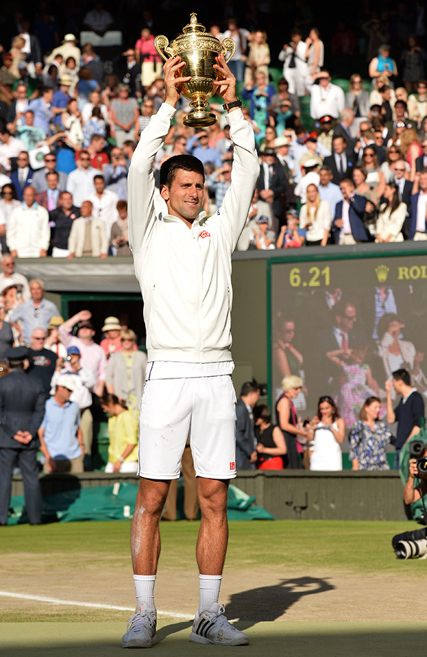 Novak Djokovic lifts the winners trophy after beating Roger Federer on centre court of the Wimbledon Championships at Wimbledon on July 6, 2014 in London, England. (Photo by Karwai Tang/WireImage)
