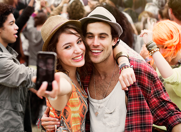 MODEL RELEASED, Couple taking self-portrait at music festival 2012