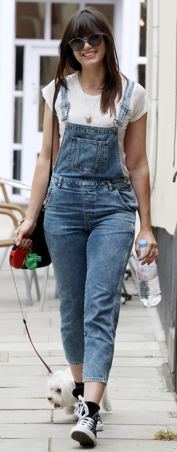 Daisy Lowe walking dog Monty in Primrose Hill wearing denim dungarees, 7th July 2015