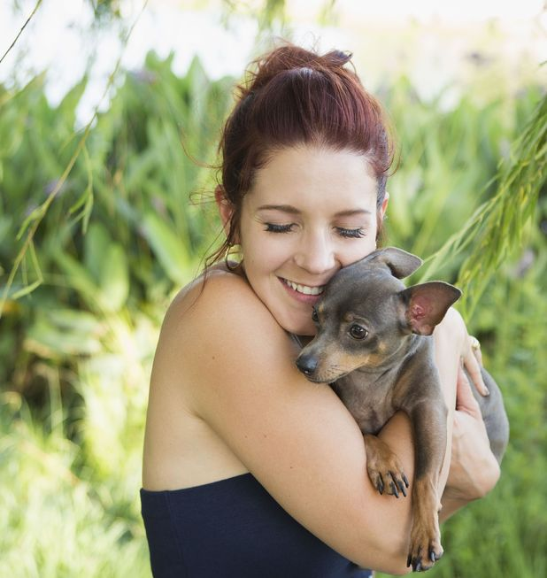 Woman hugging her dog - Capital One survey shows Brits spend £3.4 billion on pet presents each year