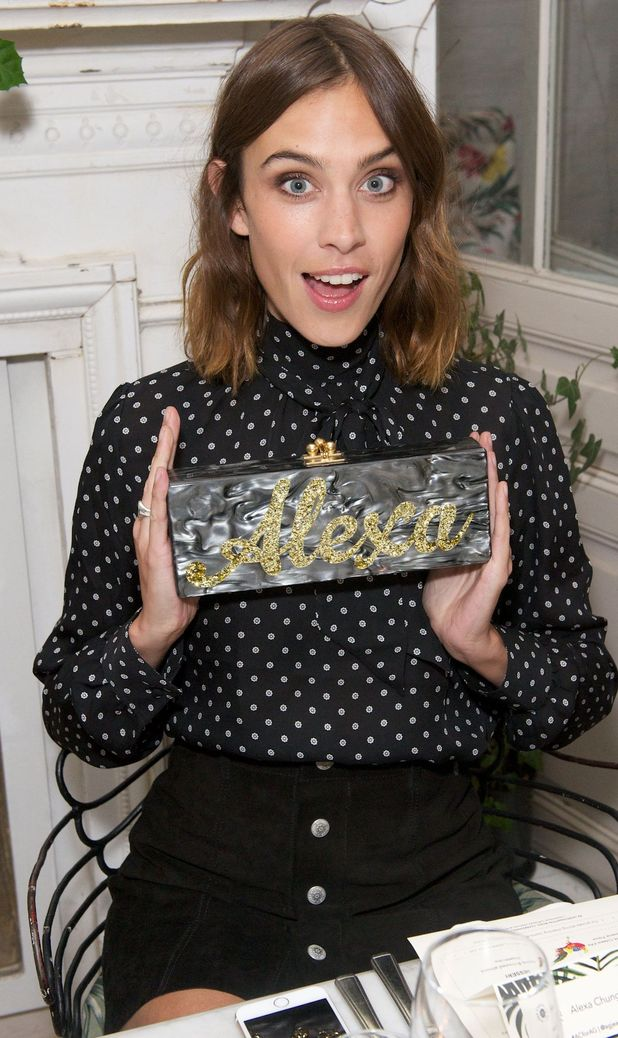 Alexa Chung shows off her clutch bag at the AG London Dinner in London 15th July 2015