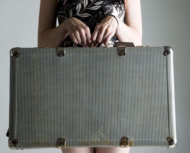 Young woman with suitcase - Carers Trust survey shows 68 per cent of carers won't go on holiday this year.