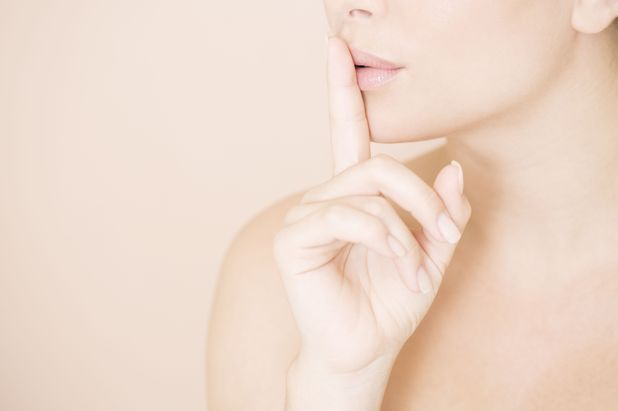 A woman with her finger to her lips.