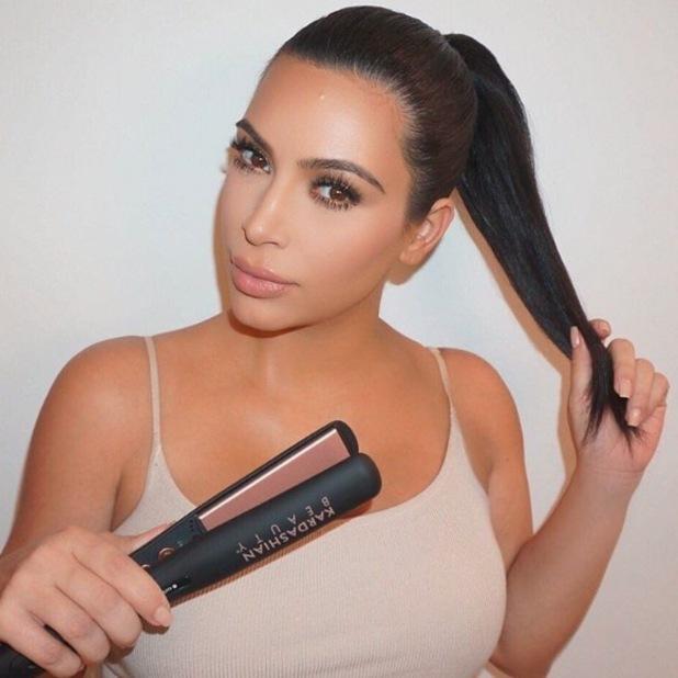 Kim Kardashian straightening hair with Kardashian Beauty hair straighteners 13th November 2015