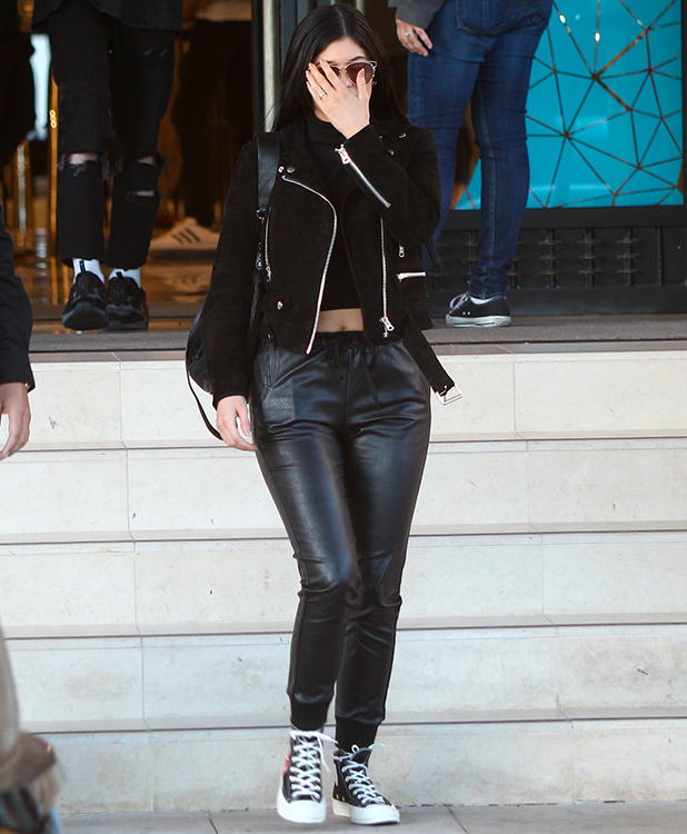 Kylie Jenner covers her face as she leaves Barneys New York in Beverly Hills as she shows her midriff in a black cropped sweater and black leather jacket with a pair of leather trousers