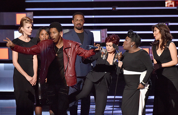 TV personality Sharon Osbourne kicks a stage crasher while Osbourne and fellow 'The Talk' hosts Sheryl Underwood (2nd from L) and Julie Chen (R) accept the award for Favorite Favorite Daytime TV Hosting Team during the People's Choice Awards 2016 at Microsoft Theater on January 6, 2016 in Los Angeles, California. (Photo by Lester Cohen/WireImage)