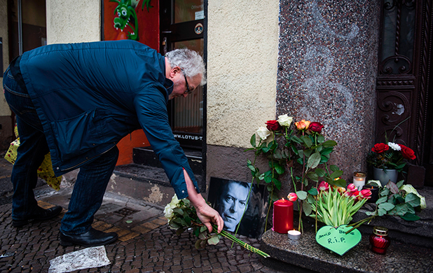 David-Bowie-fan Dirk Turnage puts down a tribute to British rock legend David Bowie outside his former home in Berlin's Hauptstrasse 155 on January 11, 2016. British rock music legend David Bowie has died after a long battle with cancer, his official Twitter and Facebook accounts said. / AFP / ODD ANDERSEN (Photo credit should read ODD ANDERSEN/AFP/Getty Images)