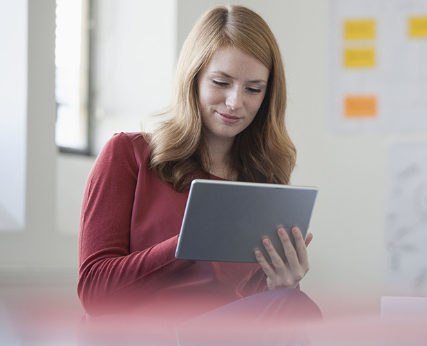 MODEL RELEASED Young woman in office holding digital tablet 2015