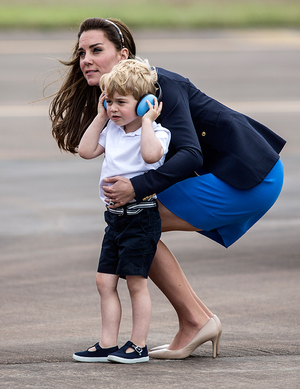 Britain's Prince George (2nd L) sits in a 'Squirrel' helicopter with his mother Catherine, Duchess of Cambridge and father Prince William during a visit to the Royal International Air Tattoo at RAF Fairford in western England, on July 8, 2016.